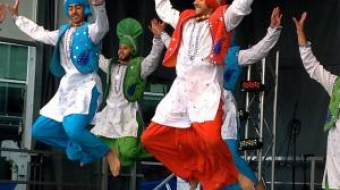 Male Bhangra dancers mid-jump on-stage, performing in Celebrate the Harvest.