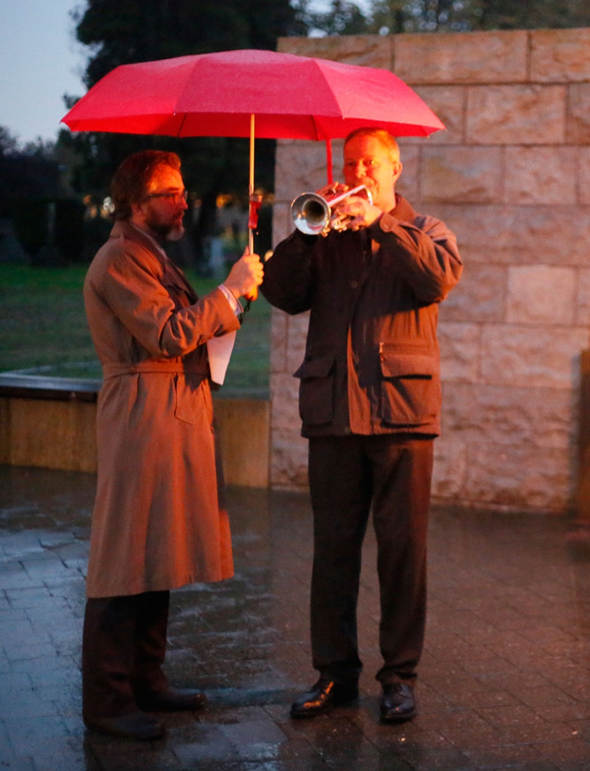 Mark Haney shields a fellow musician from the elements